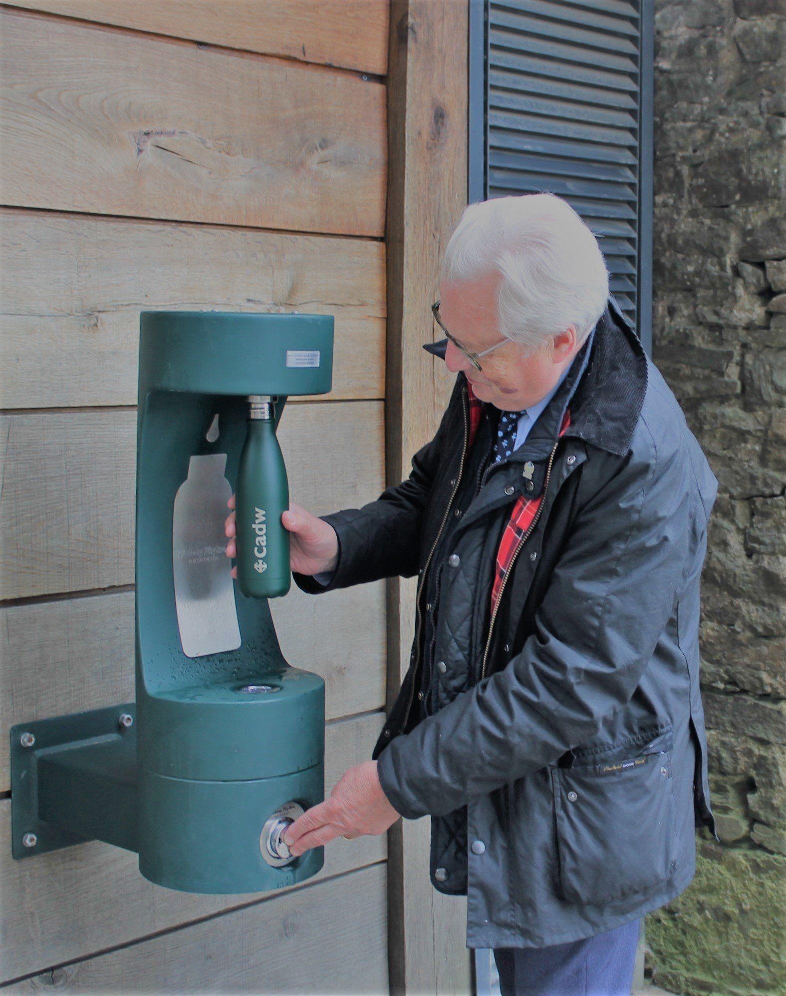 A man refilling his water bottle at a green bottle filler.