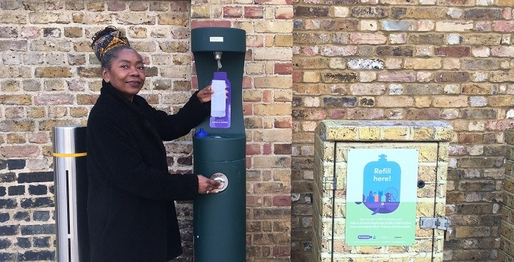 Woman refilling her bottle at an outdoor refill station in Windrush Square.