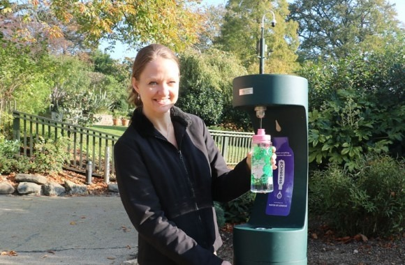 Woman refilling at an outdoor bottle refill station in Horniman Museum and Gardens.