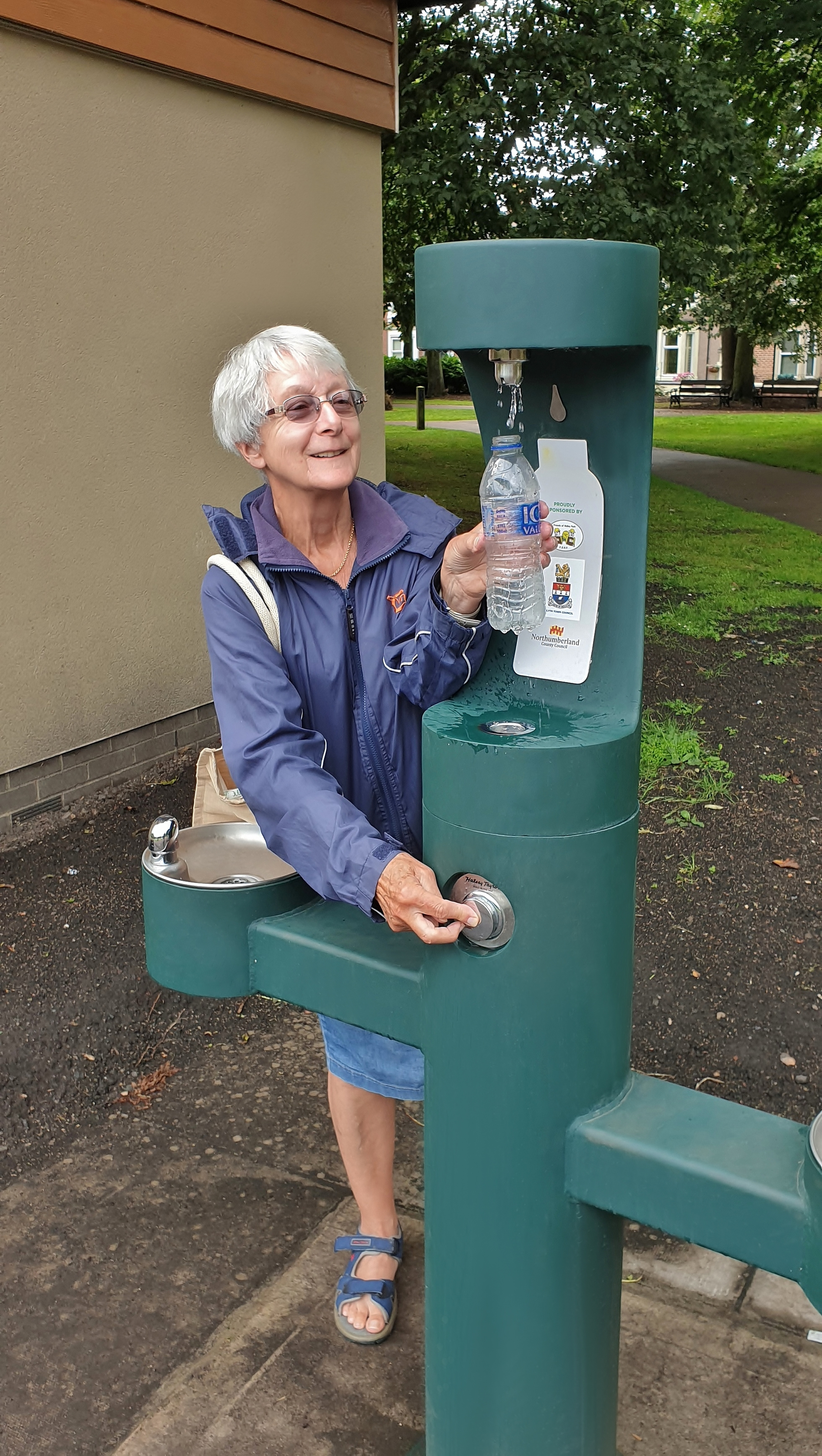 An elderly woman refilling her water bottle at the new drinking fountain.