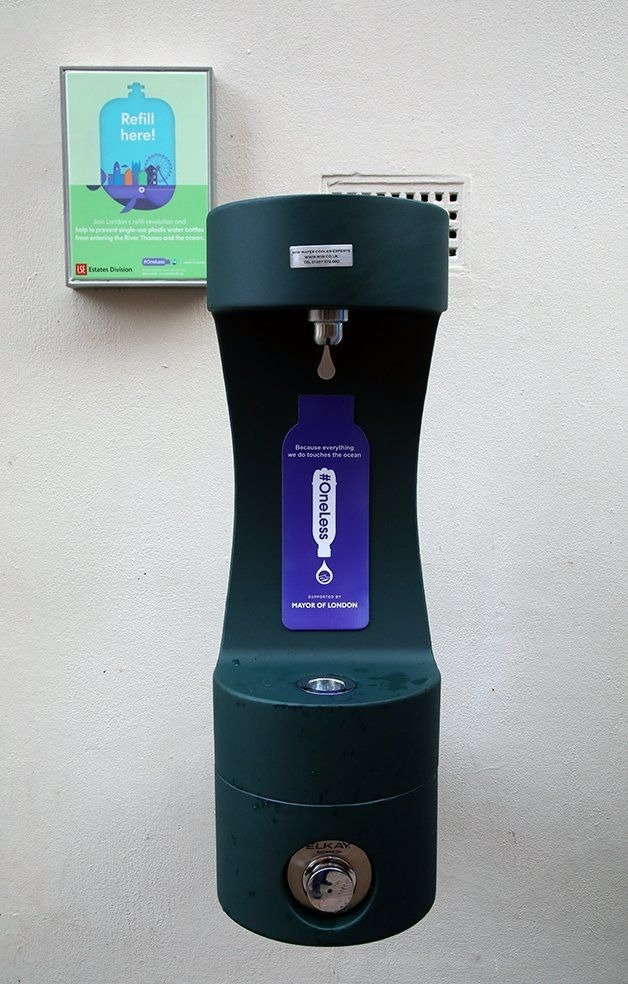 Green #OneLess drinking fountain mounted to the wall.