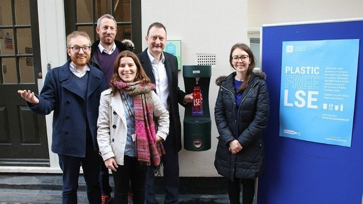 Group of people smiling at the new London School of Economics drinking fountain.