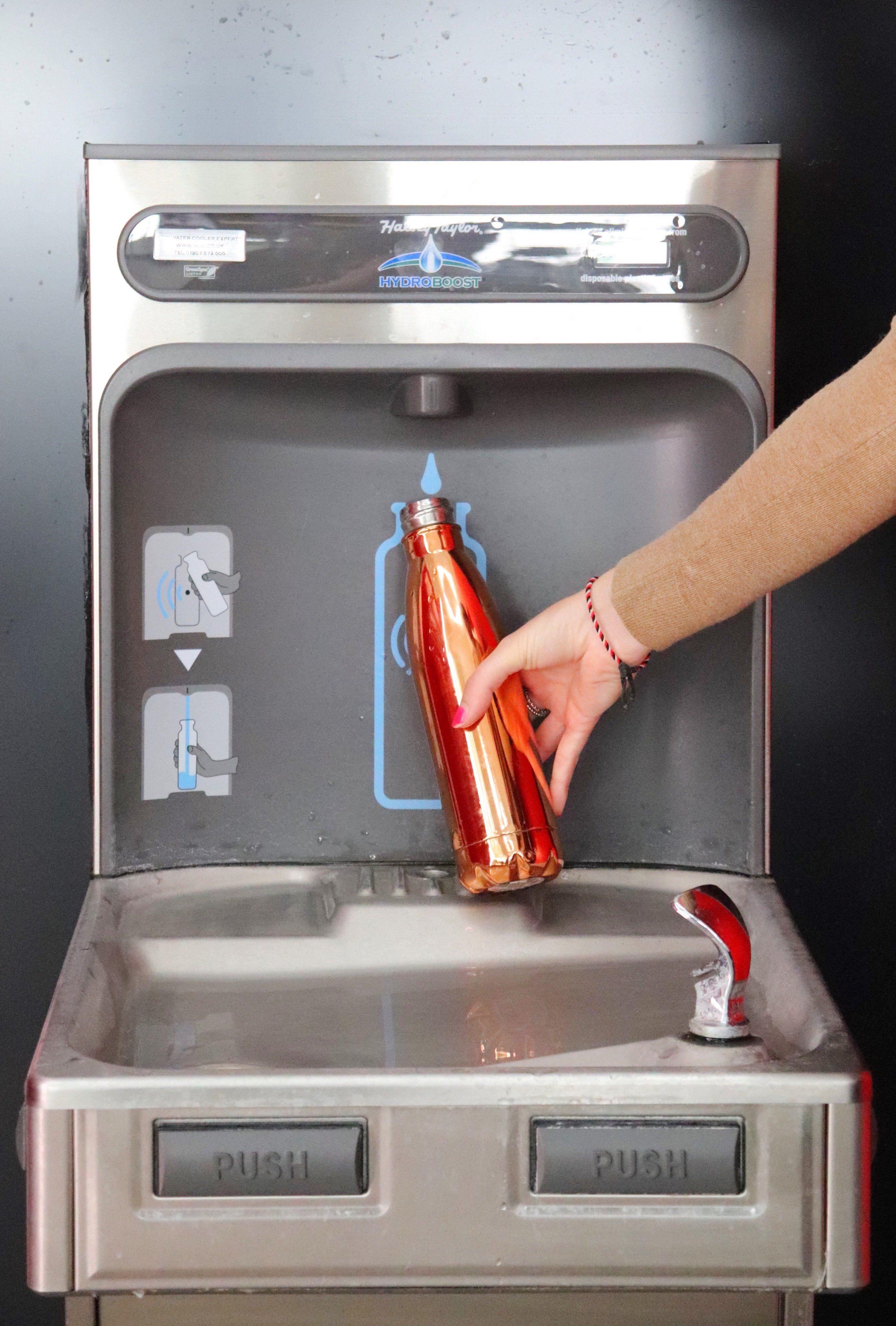 Customer refilling their reusable water bottle at the new bottle filler.