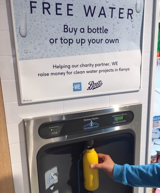 Yellow bottle being refilled at the new bottle filler in Boots.
