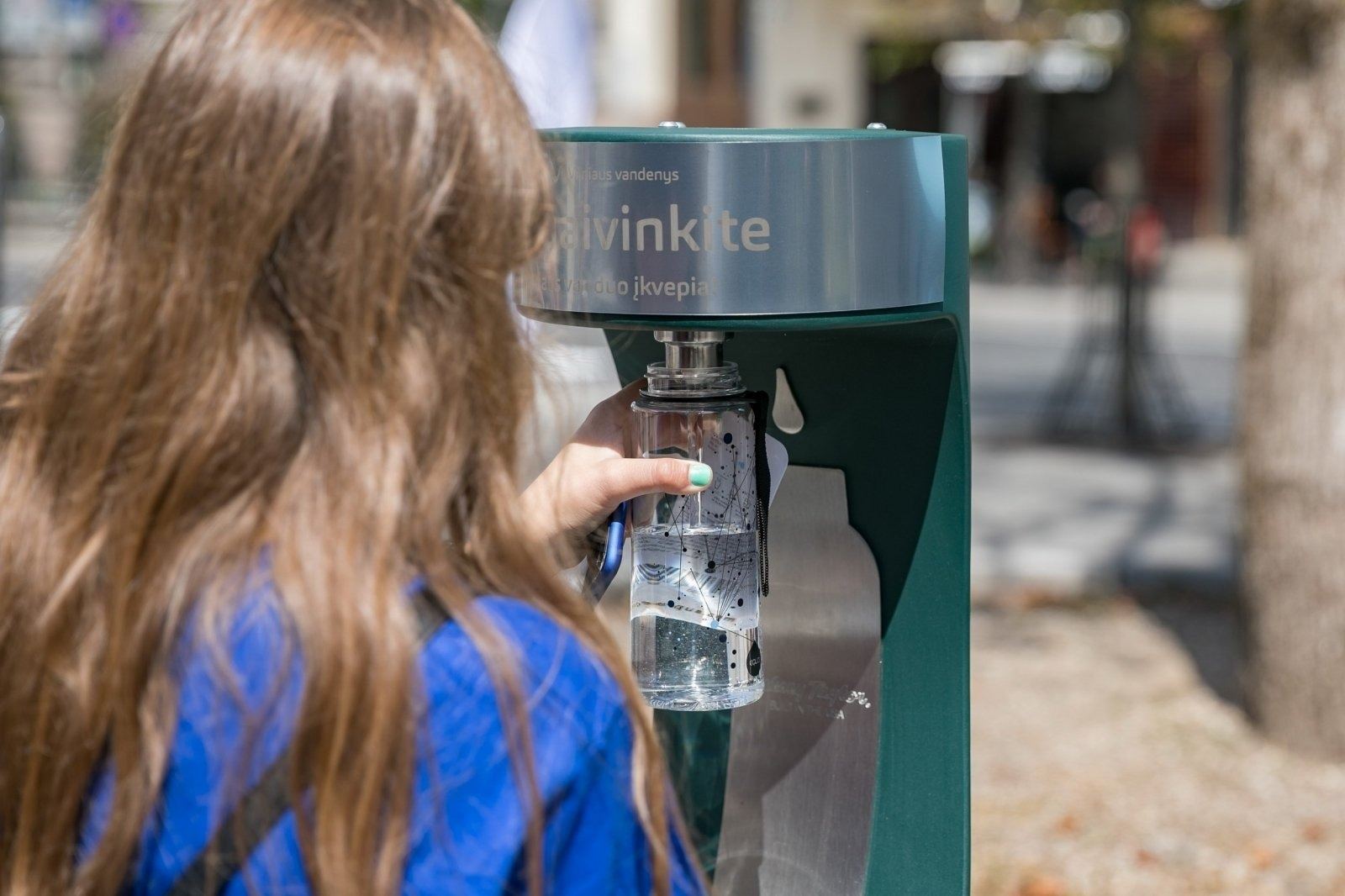 Girl with brown hair refilling her water bottle at the new public drinking fountain in Vilnius, Lithuania