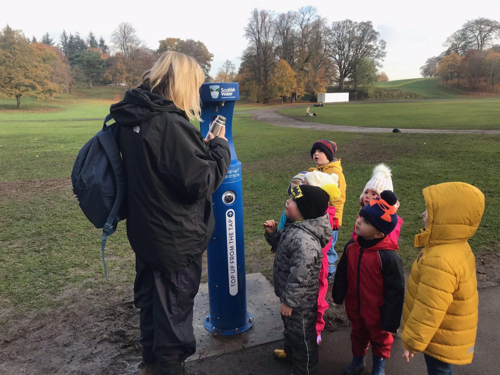 Teacher and children refilling their water bottles at the new bottle filler.