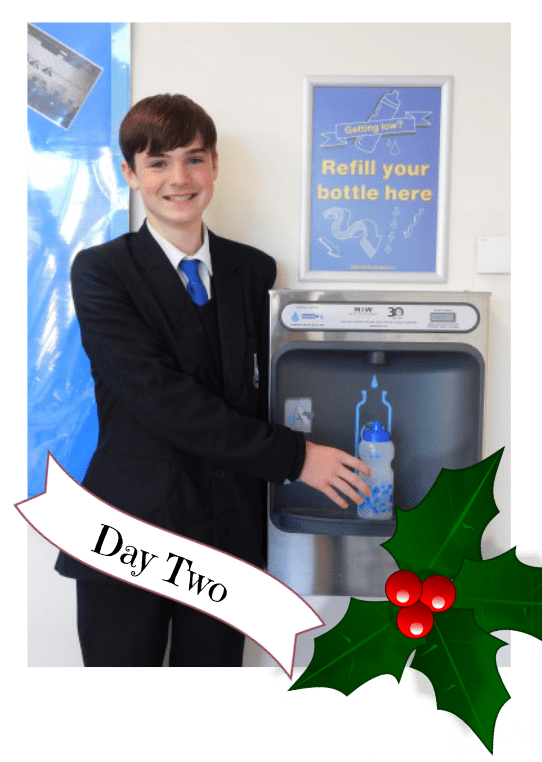 One of the pupils posing with our bottle refill station installed in their school.