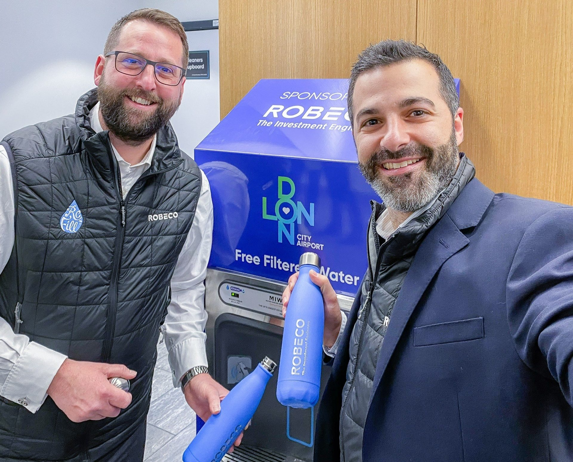 Happy People Refilling From The New Branded Bottle Filling Station At The Airport