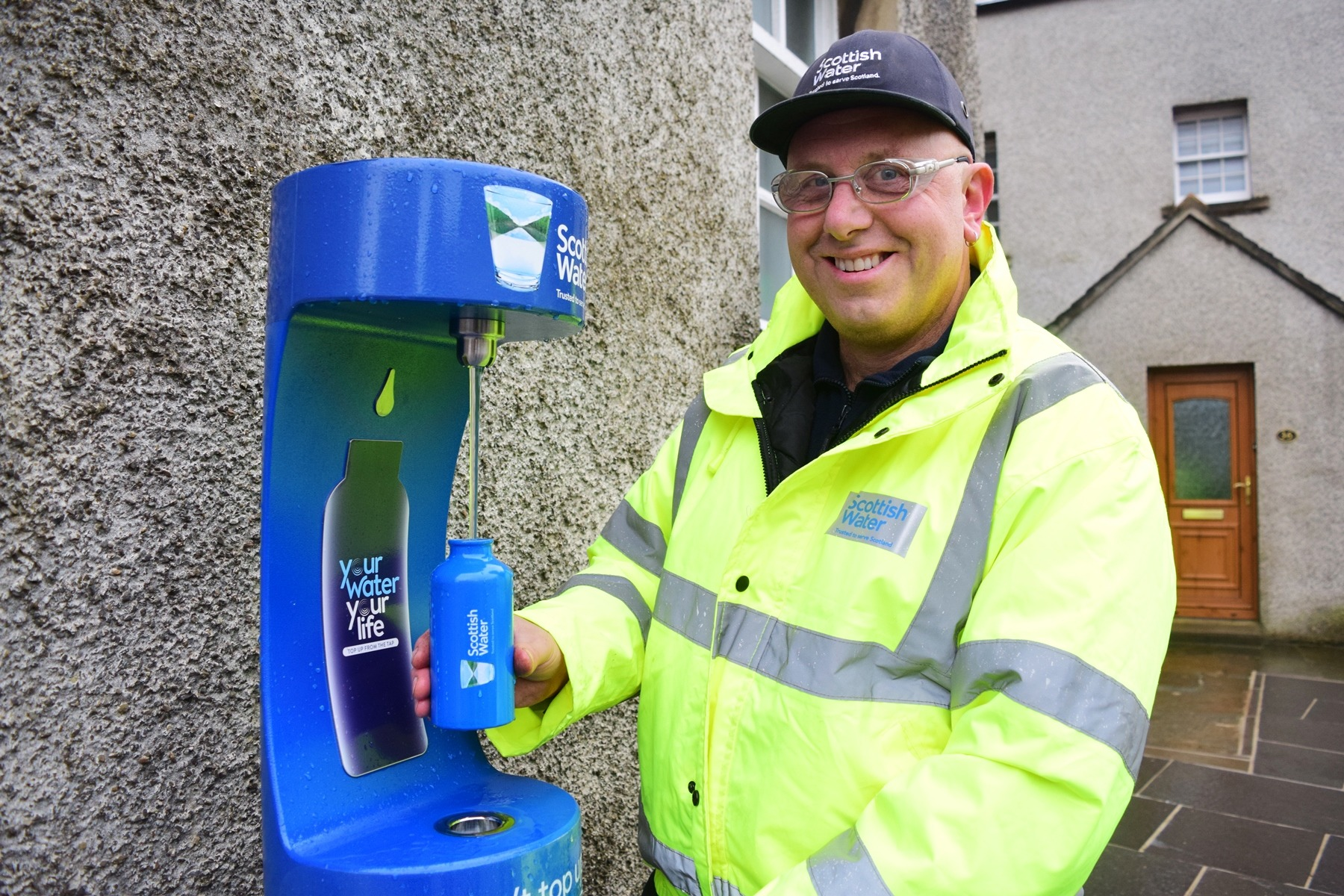 Man refilling his reusable bottle from the new water dispenser in Kirkwall
