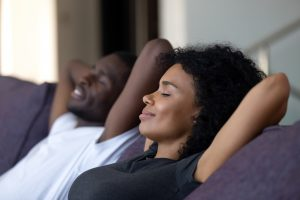 Couple sitting on a sofa relaxing with their hands behind their heads